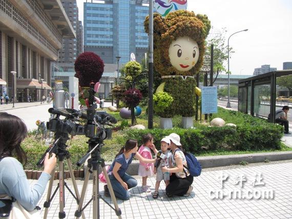 花博娃娃人形立牌前,大太阳下吸引大朋友带小朋友一起拍照.图片