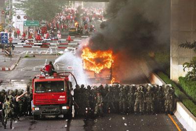 与军人对峙,烧巴士阻止他们逼近,军方则出动灭火车射水.-曼谷终图片