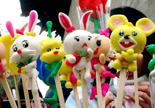 """在郑州一个庙会的面塑工艺品展台上,两只小白兔和其他小动物""""和睦相处"""