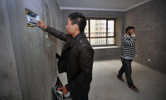 验房师张章在检查房屋的电路(10月26日摄).新华社