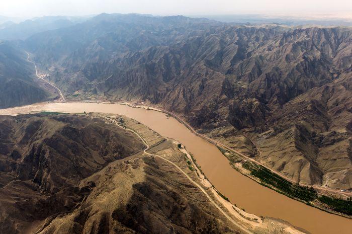 图为黄河宁夏中卫段河面蜿蜒曲折,两侧高山林立的自然景观(6月29日摄)