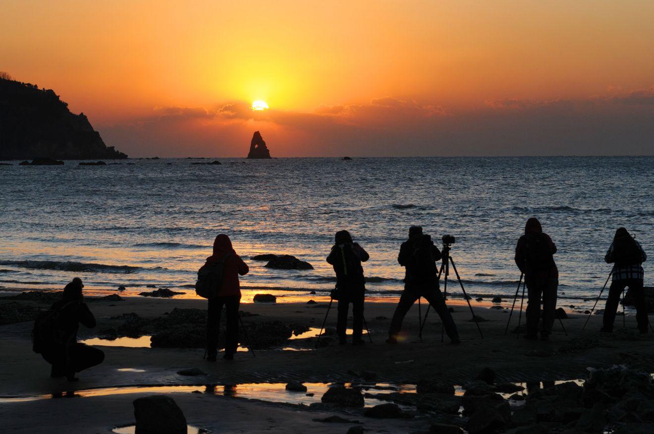 摄影爱好者在青岛石老人海滩拍摄日出