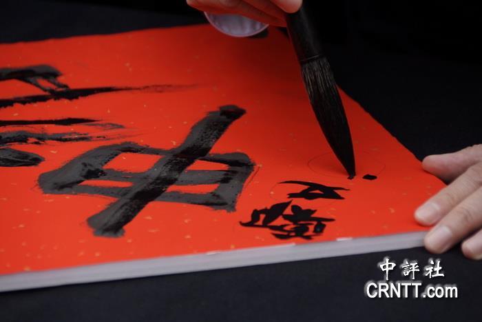 """提毛笔写自己的名字,""""灿""""字笔画多,写起来比较辛苦.(中评社"""